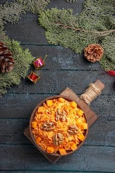 ダークブルーの背景にクルミとおいしいニンジンサラダの上面図健康サラダ色ダイエット食品ナッツ