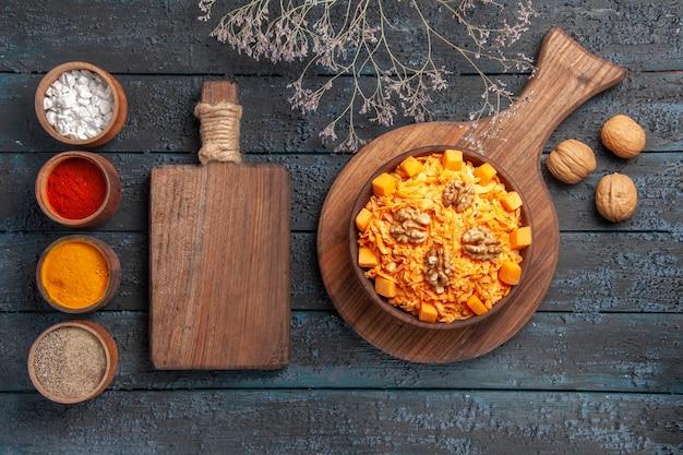 Vista dall'alto gustosa insalata di carote con noci e condimenti su insalata di noci da scrivania blu scuro dieta salute cibo colore