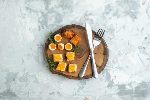 上面図ゆで卵とカトラリーを木の板に載せたおいしいキャビアサンドイッチ白い表面の食べ物朝食ランチシーフード魚のトースト食事