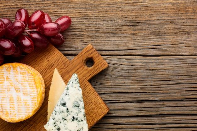 Вид сверху вкусный сыр и виноград с копией пространства