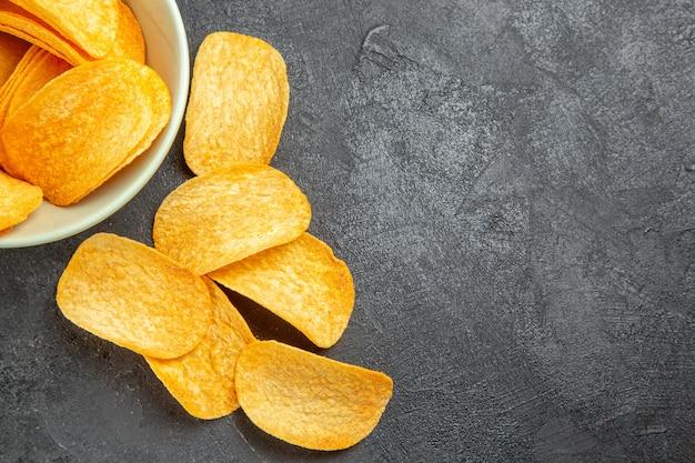 Вид сверху вкусные сырные чипсы внутри тарелки на темном фоне