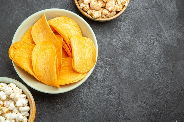 Top view tasty cheese chips with different snacks on a dark background