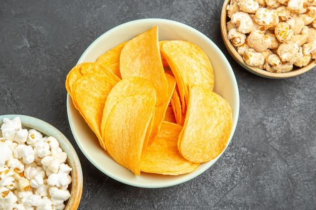 Vista dall'alto gustose patatine al formaggio con diversi snack sullo sfondo scuro