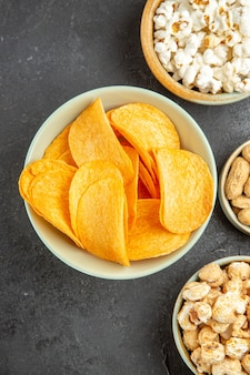 Top view tasty cheese chips with different snacks on the dark background