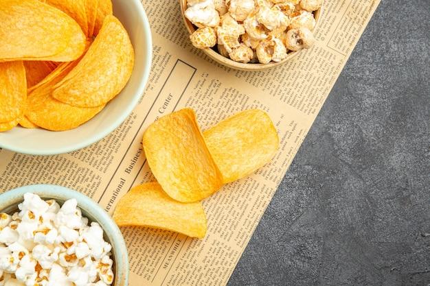 어두운 책상에서 영화 시간 동안 다양한 스낵과 함께 맛있는 치즈 칩을 봅니다.