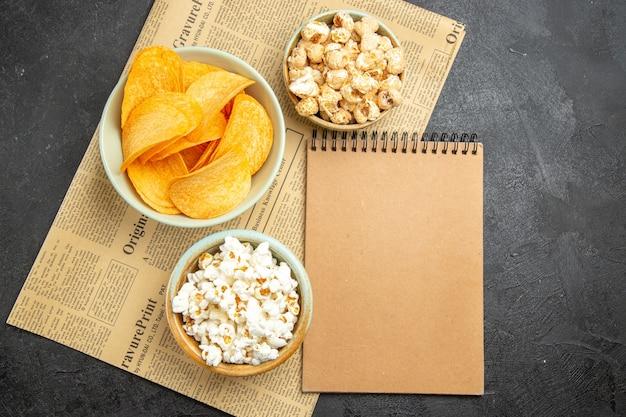 어두운 배경에서 영화 시간 동안 다른 간식과 함께 맛있는 치즈 칩을 봅니다.