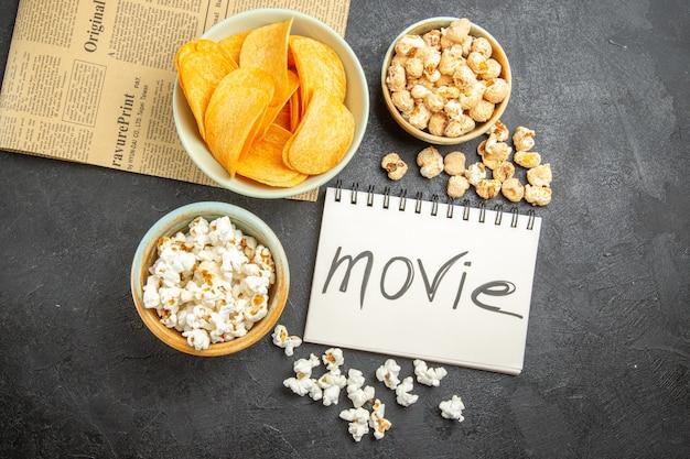 Vista dall'alto gustose patatine al formaggio con diversi snack e film scritto blocco note su sfondo scuro