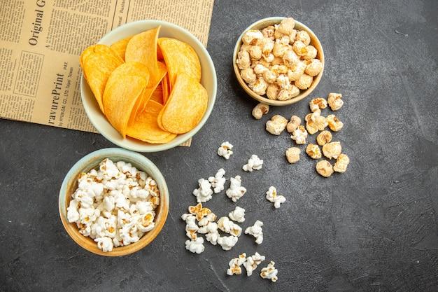 Вид сверху вкусные сырные чипсы с разными закусками на темном фоне