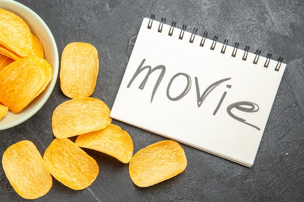 灰色の背景に映画で書かれたメモ帳とプレート内のおいしいチーズcipsの上面図