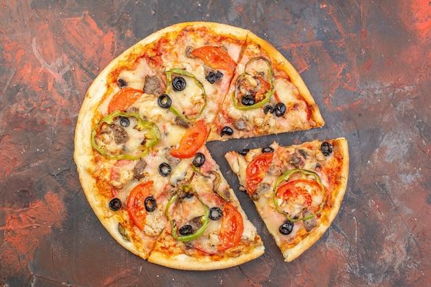 Вид сверху вкусной сырной пиццы, нарезанной и поданной на темно-коричневой поверхности