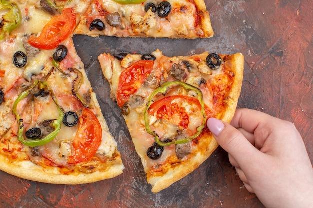 Vista dall'alto gustosa pizza al formaggio affettata e servita su una superficie marrone scuro