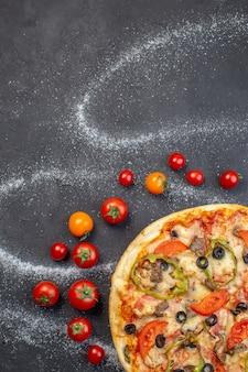 Vista dall'alto gustosa pizza al formaggio con pomodori rossi su superficie scura