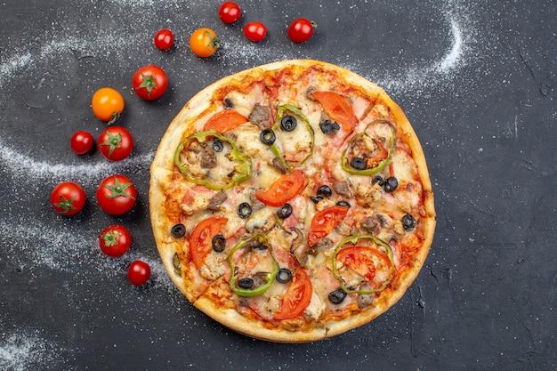 暗い表面に赤いトマトの上面図おいしいチーズピザ