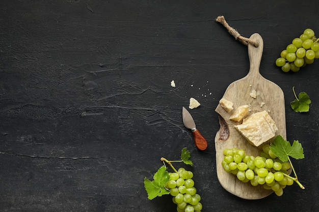 Top view of tasty cheese plate with fruit, grape on black desk.