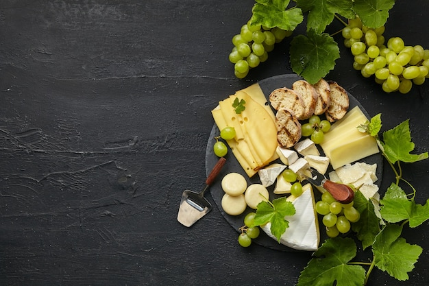 Top view of tasty cheese plate with fruit, grape on a circle kitchen plate on black stone