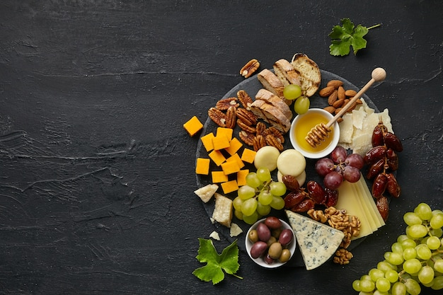 Top view of tasty cheese plate with fruit, grape, nuts and honey on black desk.