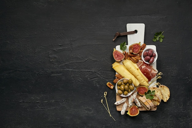 Top view of tasty cheese plate with fruit, grape, nuts, olives and toasted bread on a wooden kitchen plate on the black stone background, top view, copy space. gourmet food and drink.