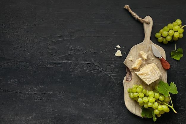 Vista dall'alto del gustoso piatto di formaggi con frutta, uva su un piatto da cucina in legno su sfondo di pietra nera