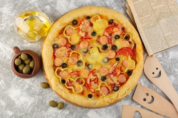 Вид сверху вкусной сырной пиццы с сосисками из черных оливок и красными помидорами вместе с маслом и оливками на сером столе, выпечка из итальянского теста