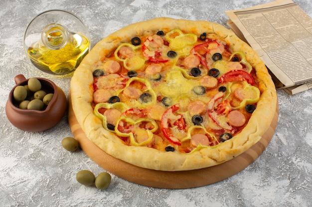 Вид сверху вкусной сырной пиццы с сосисками из черных оливок и красными помидорами вместе с маслом на сером столе, выпечка из итальянского теста быстрого питания