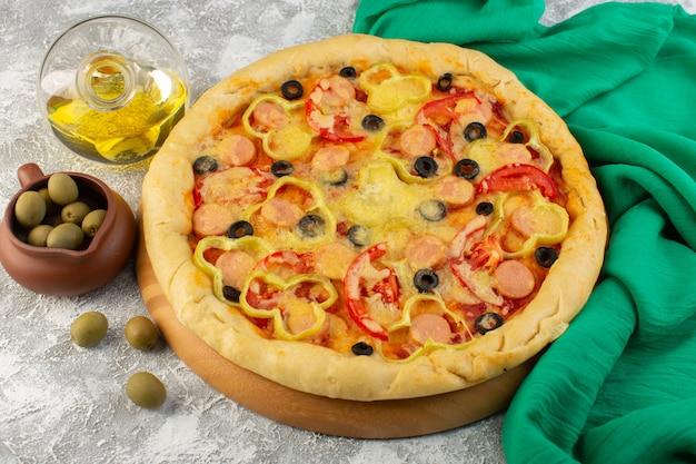 Vista dall'alto gustosa pizza di formaggio con olive nere salsicce e pomodori rossi insieme a olio sulla scrivania grigia fast-food pasta italiana pasto cuocere