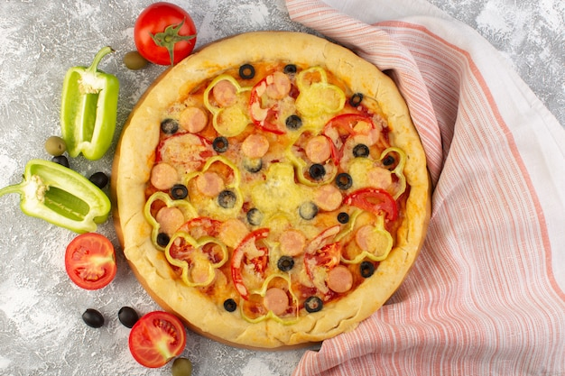 Top view tasty cheesy pizza with black olives sausages and red tomatoes on the grey background fast-food italian dough meal bake