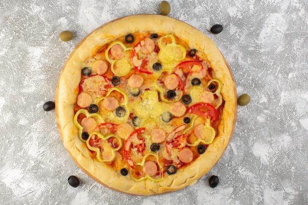 Вид сверху вкусной сырной пиццы с оливками, сосисками и красными помидорами на сером столе фаст-фуд итальянское тесто