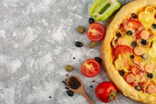 Vista dall'alto gustosa pizza di formaggio con olive salsicce e pomodori rossi sul pasto di pasta italiana fast-food sfondo grigio