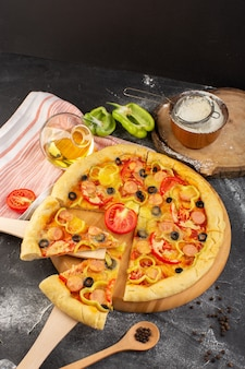 Вид сверху вкусная сырная пицца с красными помидорами, маслинами и сосисками на темном столе с маслом и свежими помидорами фастфуд итальянское тесто запекать
