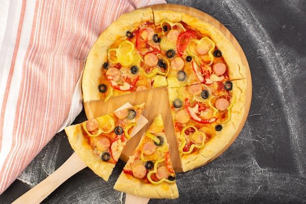 Вид сверху вкусная сырная пицца с красными помидорами, маслинами, болгарским перцем и сосисками на сером фоне, фаст-фуд, итальянское тесто, еда, выпечка