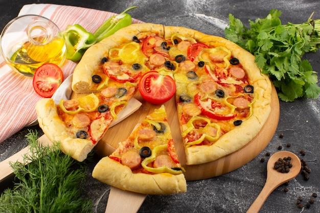 Вид сверху вкусная сырная пицца с красными помидорами, черными оливками, зеленью и сосисками на темном столе, фаст-фуд, выпечка из итальянского теста