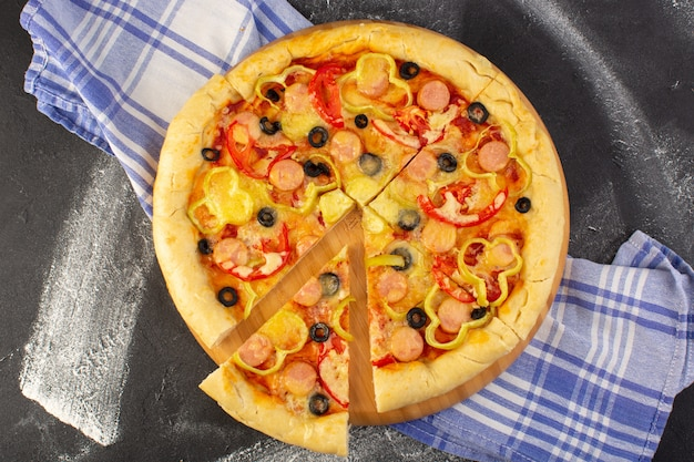 Top view tasty cheesy pizza with red tomatoes black olives and sausages on the dark background with towel fast-food italian dough