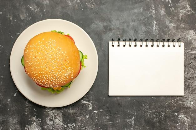 暗い表面のサンドイッチファーストフードパンに野菜とトップビューのおいしいチキンバーガー