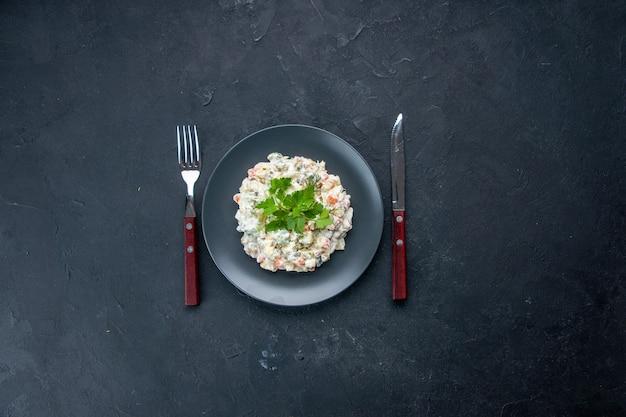 上面図さまざまなゆで野菜とマヨネーズをプレートの内側に置いたおいしいチキンサラダ、暗い表面の食用色素混合食用食用色素