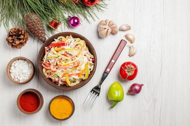 Vista dall'alto gustosa insalata di pollo con condimenti su insalata di spuntini di carne fresca del pavimento bianco