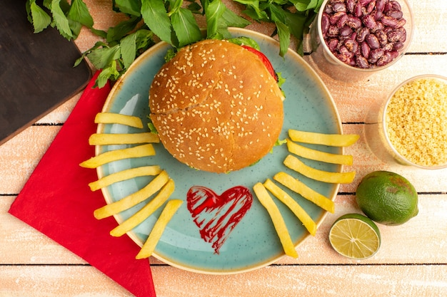 Top view of tasty chicken sandwich with green salad and vegetables inside plate with french fries on wooden cream surface