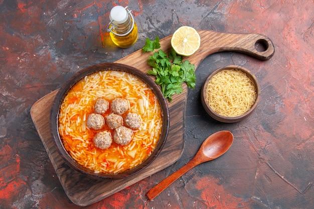 Vista dall'alto di gustosa zuppa di pollo con noodles su tagliere di legno e pasta cruda olio verde bottiglia in una piccola ciotola su sfondo scuro