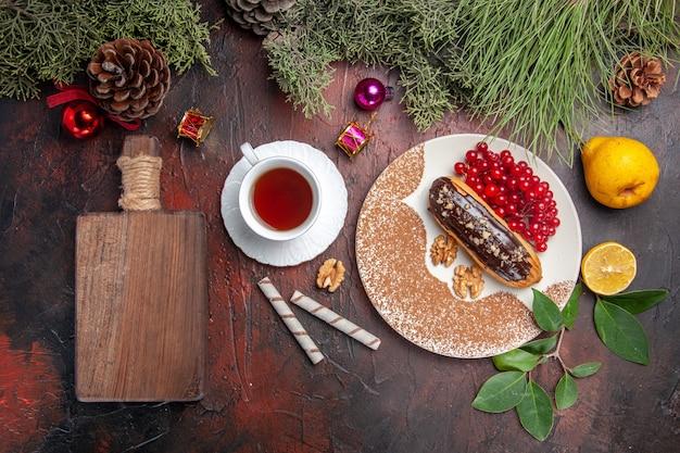 ダークテーブルのパイケーキデザートスウィートに赤いベリーとお茶を添えたトップビューのおいしいチョコエクレア