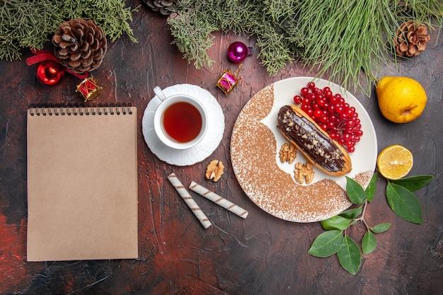 ダークテーブルのパイケーキデザートスウィートに赤いベリーとおいしいチョコエクレアの上面図