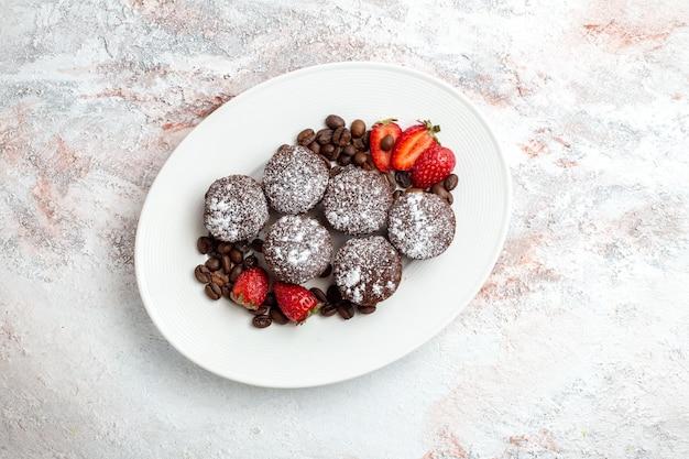 Vista dall'alto gustose torte al cioccolato con fragole e gocce di cioccolato su superficie bianca