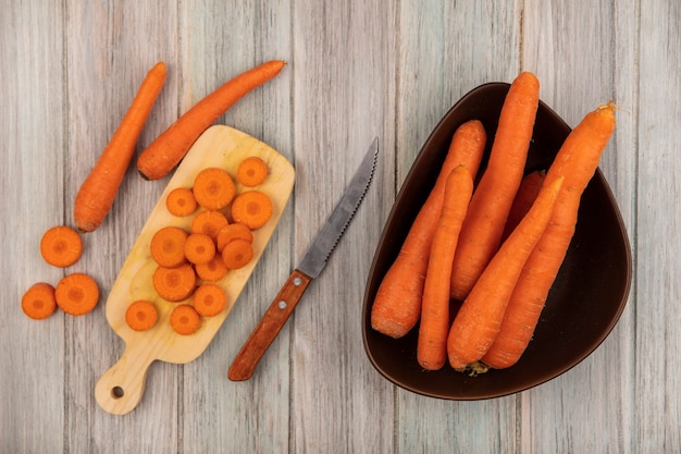 Top view of tasty chopped carrots on a wooden kitchen board with knife with carrots on a bowl on a grey wooden background