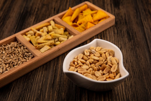 Top view of tasty cone shape corn snacks on a wooden divided plate with shelled sunflower seeds with pine nuts on a bowl on a wooden table