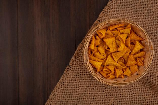 Vista dall'alto di gustosi spuntini di mais fritto a forma di cono su un secchio su un panno di sacco su un tavolo di legno con spazio di copia