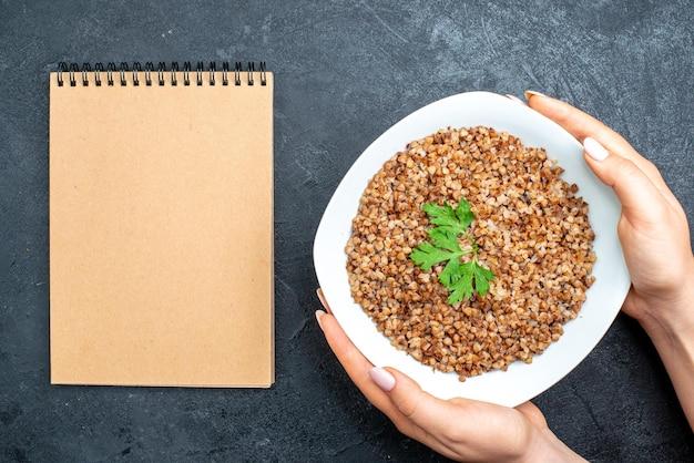 Vista dall'alto gustoso grano saraceno cotto all'interno del piatto con blocco note su spazio grigio