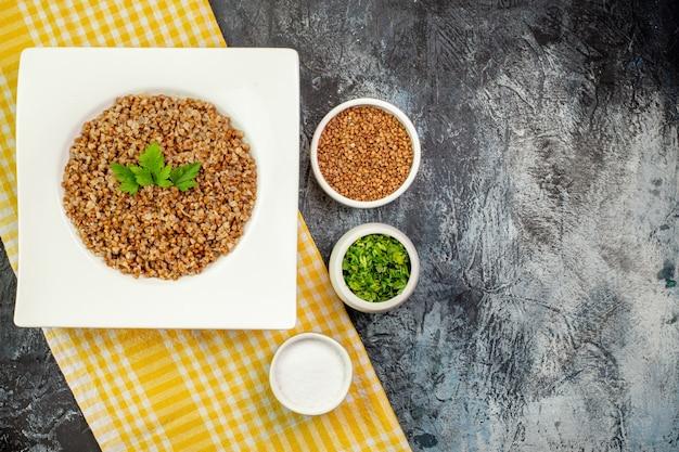Vista dall'alto gustoso grano saraceno cotto all'interno di un piatto bianco con verdure su un tavolo grigio chiaro