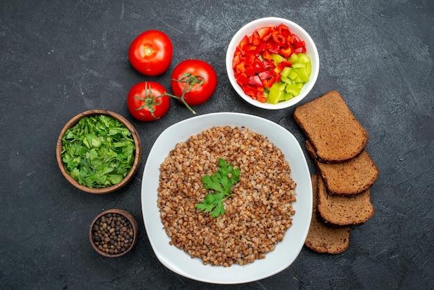 어두운 공간에 어두운 빵 덩어리와 채소와 함께 상위 뷰 맛있는 요리 메밀