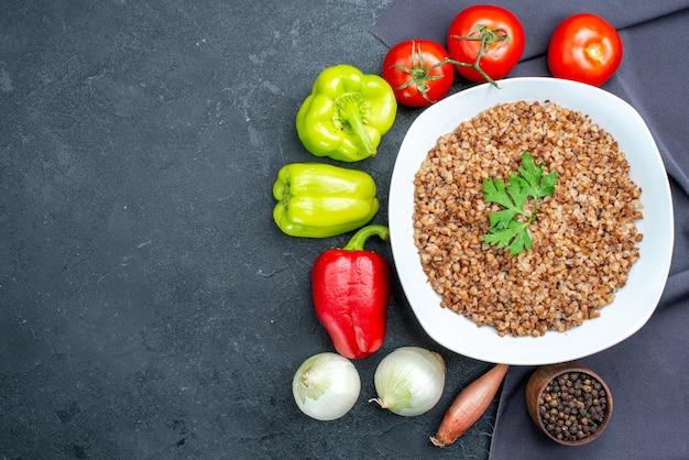 Vista dall'alto gustoso grano saraceno cotto con verdure fresche su grigio