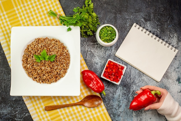 Vista dall'alto gustoso grano saraceno cotto con verdure e peperoni sul tavolo grigio chiaro