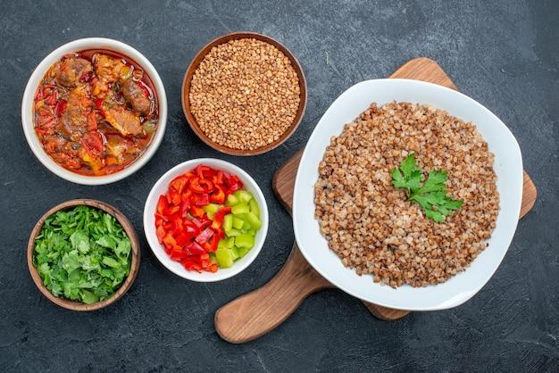 Vista dall'alto gustoso grano saraceno cotto con zuppa di verdure e verdure su grigio