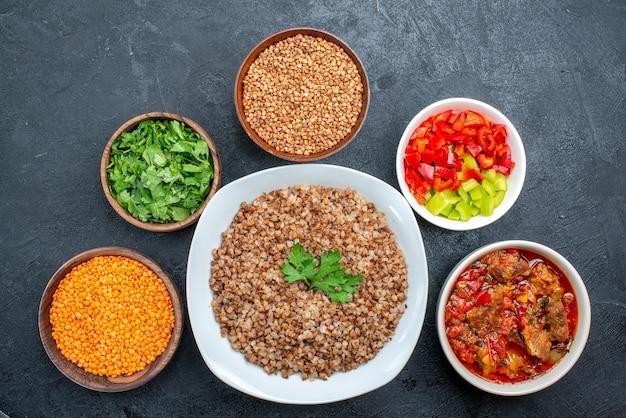 Vista dall'alto gustoso grano saraceno cotto con verdure e verdure su grigio